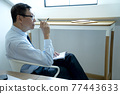 Smart businessman sitting happily thinking on a chair 77443633