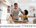 Black son enjoying playing with his father while doing bakery 77445874