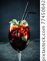 Mulled Wine in a Glass with Straws in Restaurant on Black Background 77450642