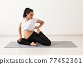 Young flexible pregnant woman doing gymnastics or yoga on rug on the floor on white background. The concept of preparing the body for easy childbirth 77452361