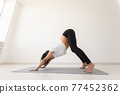 Young flexible pregnant woman doing gymnastics on rug on the floor on white background. The concept of preparing the body for easy childbirth 77452362