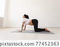 Young flexible pregnant woman doing gymnastics on rug on the floor on white background. The concept of preparing the body for easy childbirth 77452363