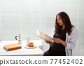 Side view of happy young beautiful woman reading book while having morning breakfast with coffee and croissants on background of blinds. Good morning concept and pleasant lunch break 77452402