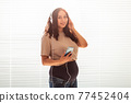 Curly-haired brunette pacified pregnant woman listens to music using smartphone and headphones. Concept of a soothing mood before meeting baby. Copy space. 77452404