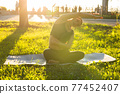 Peaceful young positive pregnant woman in gymnastic suit does yoga and meditate sitting on mat on green grass on sunny warm summer day. Concept of preparation for childbirth and positive attitude 77452407