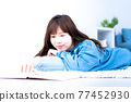 Young woman lying down in the living room and reading 77452930