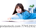 Young woman lying down in the living room and reading 77452932