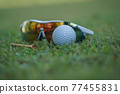 The golf ball is on the golf green, the background is blurred with the sunglasses and there is a tee placed next to it. 77455831