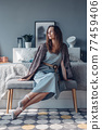 Woman at home in bedroom sitting on bedside bench. 77459406