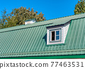 The window on green roof of a farm barn 77463531