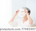 closeup senior asian woman's face and facial mask 77465997