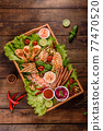 Composition of sausages, chicken, pork and shrimp prepared on grill, as well as vegetables prepared on grill with spices and herbs 77470520