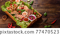 Composition of sausages, chicken, pork and shrimp prepared on grill, as well as vegetables prepared on grill with spices and herbs 77470523