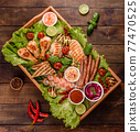 Composition of sausages, chicken, pork and shrimp prepared on grill, as well as vegetables prepared on grill with spices and herbs 77470525