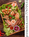 Composition of sausages, chicken, pork and shrimp prepared on grill, as well as vegetables prepared on grill with spices and herbs 77470531
