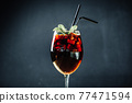 Mulled Wine in a Glass with Straws in Restaurant on Black Background 77471594