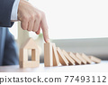 Male hand stopping falling wooden blocks in front of toy house closeup 77493112