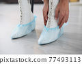 Woman putting shoe covers on her feet in white shoes closeup 77493113