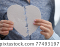 Male and female hands connecting white heart from puzzle closeup 77493197