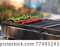 Fresh tomatoes and peppers on skewers frying on grill closeup 77493243