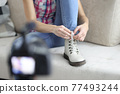 Woman blogger tying shoelaces on her shoes and filming closeup 77493244