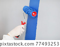 Builder in protective gloves painting white wall blue with roller closeup 77493253