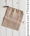 Tote bag with drawstring mockup of small eco sack made from jute hessian canvas or natural hemp burlap flat lay on white wood background from top view 77501823