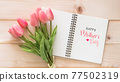 Happy Mother Day celebration greeting on white note book page background with tulip flower gift for mom on wood backdrop 77502319