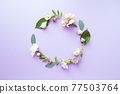 Round frame wreath with pink roses, white flowers, branches, leaves and petals on purple background. Flat lay, top view 77503764