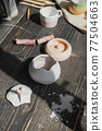 Art of pottery. Still life of pottery making tools, brushes and different ceramic vases and bowls in clay studio 77504663