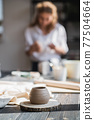 Close-up of a woman potter sculpts a brown clay pot on the background of a wooden table in the workshop 77504664