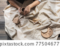 Woman sitting by table, kneading clay and making earthenware at lesson 77504677