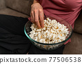 popcorn while watching a movie and broadcasting on the couch at home 77506538