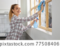Smiling Woman Washing Window with Sponge Rag, Cleaning Window, Wiping Dirt 77508406