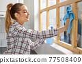Beautiful Woman Washing Window with Sponge Rag, Cleaning Window, Wiping Dirt 77508409