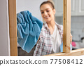 Female cleaning window glass with blue rag. Close-up photo of rag. Spring cleanup, housework concept 77508412