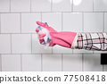 Hand in rubber glove holding sponge in foam, isolated on white tiled wall 77508418