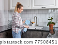 Side View Portrait Of Nice Pleasant Caucasian Woman, Removing Dirt From Table And Sink 77508451