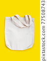 White fabric bag on yellow background. 77508743