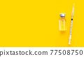 Bottle of vaccine and syringe on yellow background with copy space. 77508750