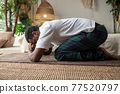 African man doing yoga at home, having rest in balasana or child pose, relaxing body muscles between asana 77520797