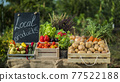 A counter with fresh vegetables at a small farmers market 77522188