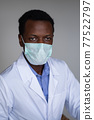 Young black man wearing a white coat and face mask 77522797