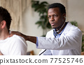 African doctor examining young male patient listening lungs and heart 77525746