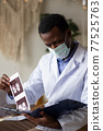 African doctor analyzing ultrasound results of his pacient. 77525763