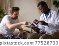 African doctor analyzing ultrasound results of his pacient. 77528733