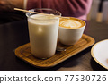 Iced Thai tea latte in glass mug in a coffee shop. 77530726