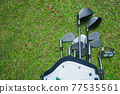 Closeup old golf bags on green. Set of golf clubs over green field background. 77535561