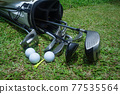 Closeup old golf bags on green. Set of golf clubs over green field background. 77535564