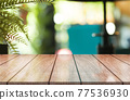 Empty wooden table top with lights bokeh on blur restaurant background. 77536930